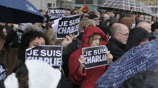 """Des Français se recueillent pendant une minute de silence en hommage aux victimes de l'attaque de """"Charlie Hebdo"""", le 8 janvier 2015, à La Défense. (ERIC PIERMONT / AFP)"""