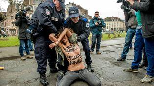 Une militante des Femen arrêtée par la police, à proximité du tribunal correctionnel de Lille (Nord), le 10 février 2015, au moment de l'arrivée de Dominique Strauss-Kahn. (PHILIPPE HUGUEN / AFP)