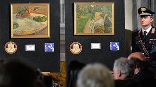 Un gendarme à côté des deux toiles retrouvées quarante-quatre ans après leur vol, le 2 avril 2014 à Rome (Italie). (ANDREAS SOLARO / AFP)