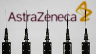 Des seringues devant le logo du groupe pharmaceutique AstraZeneca, qui teste un vaccin expérimental contre le Covid-19, ici le 12 octobre 2020 à Varsovie (Pologne). (JAKUB PORZYCKI / NURPHOTO / AFP)