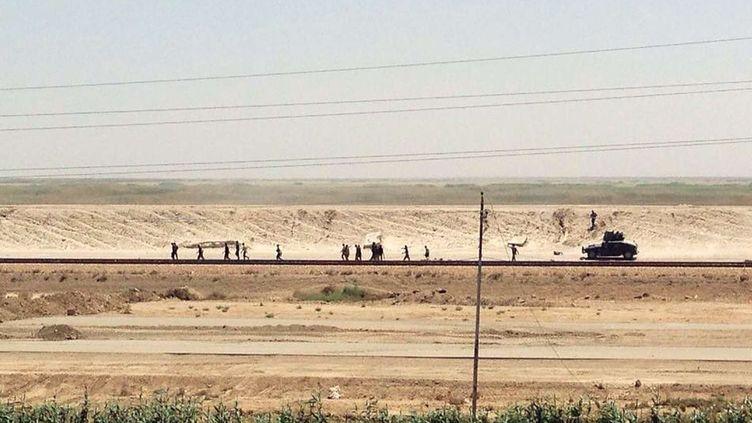 Les forces de sécurité irakiennes fuient devant l'avancée de l'organisation Etat islamique, à Ramadi, en Irak, le 17 mai 2015. ( AP / SIPA )
