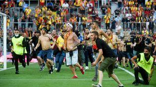 Des supporters de Lens envahissent la pelouse duStade Bollaert-Delelis à la mi-temps du derby contre Lille en Ligue 1, le 18 septembre 2021 (FRANCOIS LO PRESTI / AFP)