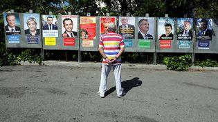 Un homme regarde les affiches des onze candidats à la présidentielle, à Saint-André-de-la-Roche (Alpes-Maritimes), le 10 avril 2017. (ERIC GAILLARD / REUTERS)