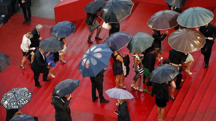 Montée des marches sous la pluie au festival de Cannes, le 22 mai 2013. (LOIC VENANCE / AFP)