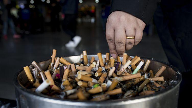 Un homme broie sa cigarette, le 28 février 2017. Photo d'illustration. (JOHANNES EISELE / AFP)