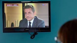 Une femme regarde Nicolas Sarkozy à la télévision sur TF1, mercredi 2 juillet 2014. (DENIS CHARLET / AFP)