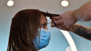 Une femme se fait couper les cheveux dans un salon de coiffure. Photo d'illustration.  (JOHN THYS / AFP)
