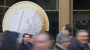 A madrid, le 6 décembre, un restaurant a collé sur sa vitrine un autocollant représentant une pièce d'un euro géante. (DOMINIQUE FAGET/AFP)