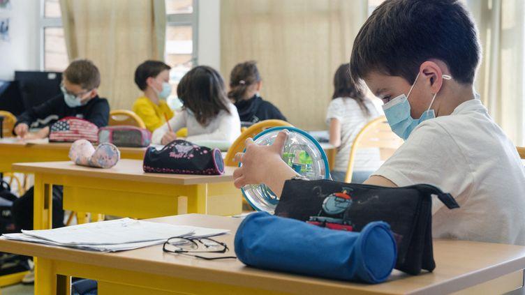 Les enfants des professionnels considérés comme essentiels ont pu continuer à suivre en présentiel les courspendant la fermeture des établissements scolaires, comme dans cette école deSaint-Julien-l'Ars (Vienne), le 9 avril 2021. (JEAN-FRANCOIS FORT / HANS LUCAS / AFP)