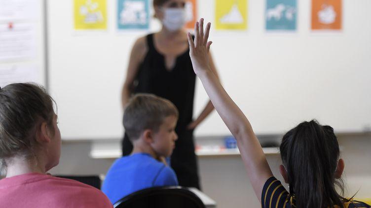 Une élève lève la main dans une salle de classe au moment de la rentrée scolaire la rentrée scolaire,le 1er septembre 2020 (photo d'illustration). (FREDERICK FLORIN / AFP)