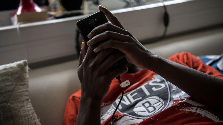 Un jeune migrant utilise son portable dans un centre de Médecins sans frontières à Pantin (Seine-Saint-Denis), le 3 juillet 2018. (CHRISTOPHE ARCHAMBAULT / AFP)