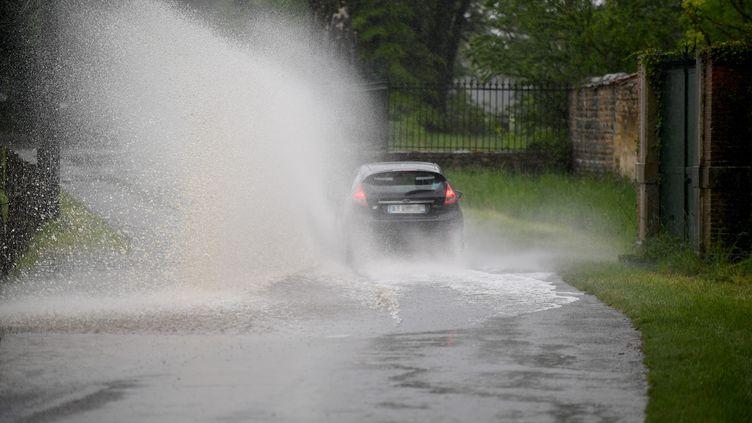 Une voiture roule sur une route inondée par la montée de l'Ain, entre Tossiat et Montagnat (Ain), le 10 mai 2021. (MAXPPP)
