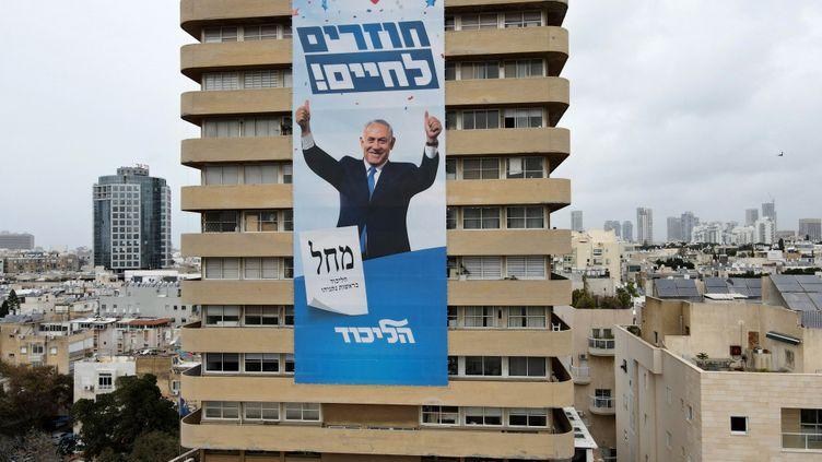 """Une affiche de campagne de Benyamin Netanyahou, avec le slogan """"Retour à la vie"""", sur la façade d'un immeuble de Tel Aviv, le 11 mars 2021. (JACK GUEZ / AFP)"""