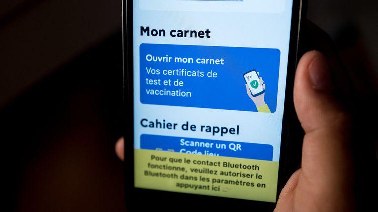 Une personne montre son certificat de vaccination sur l'application TousAntiCovid, le 12 juin 2021. (FREDERIC SCHEIBER / HANS LUCAS / AFP)