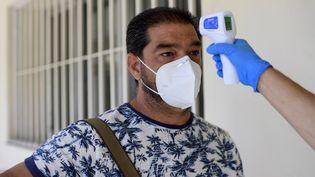 Prise de température dans un centre de test au nouveau coronavirus à Madrid (Espagne), le 17 août 2020. (OSCAR DEL POZO / AFP)