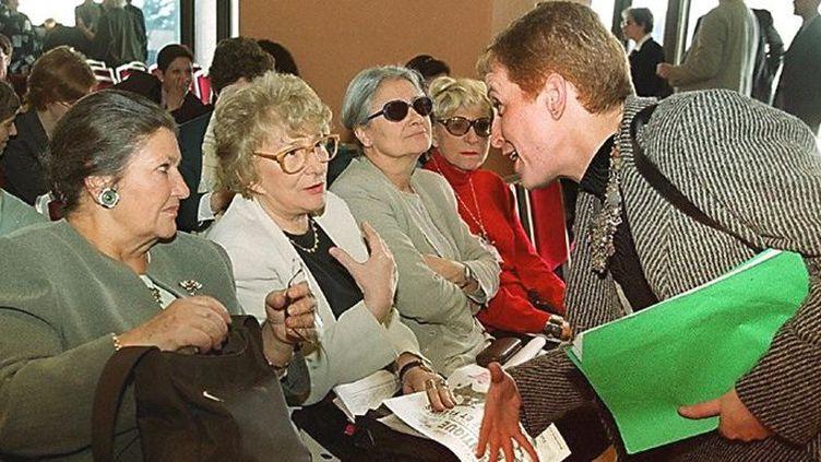 La députée Khalida Messaoudi (debout) s'entretient avec les anciennes ministres Simone Veil (à gauche) et Yvette Roudy, le 9 mars 2000 à Alger, lors d'une réunion publique organisée par les féministes algériennes sous le thème «Alger, capitale-symbole de la résistance des femmes». (HZ / AFP)