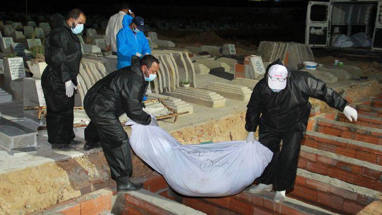 Desfossoyeurs enterrent les corps des immigrés africains, morts noyés et rejetés par la mer après le naufrage de leur bateau devant l'île de Kerkennah, le 11 juin 2020, au cimetière de Sfax. (HOUSSEM ZOUARI / AFP)