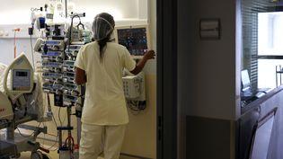 Une soignante vérifie les constantes d'un patient positif au Covid-19, le 30 juillet 2021, au Centre hospitalier de Saint-Pierre, à la Réunion. (RICHARD BOUHET / AFP)