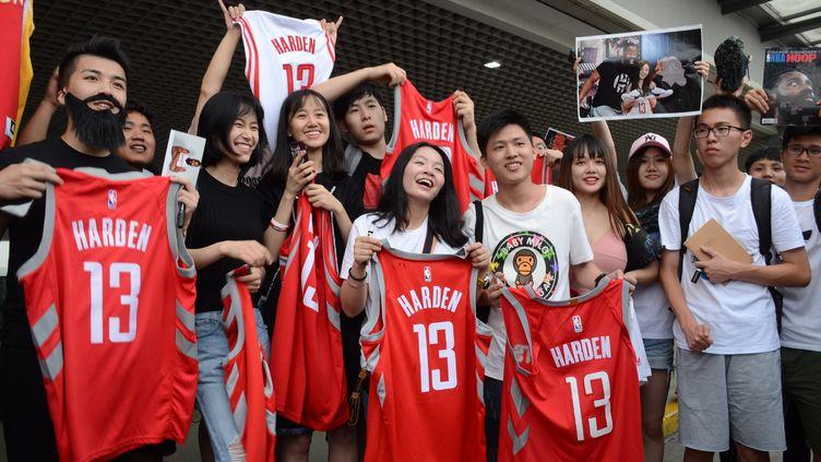 Des fans chinoise des Houston Rockets brandissent des maillots de James Harden à l'aéroport international de Shangai (Chine), le 29 juin 2018. (ZHONG FUBAO / IMAGINECHINA / AFP)