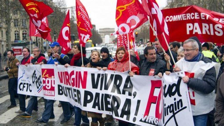Les salariés de Virgin se sont retrouvés avec des salariés de PSA, Sanofi ou encore Candia devant le magasin du groupe mardi 29 janvier 2013 à Paris sur les Champs-Elysées puis chez l'actionnaire pour défendre leurs emplois. (LIONEL BONAVENTURE / AFP)