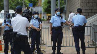 Des policiers devant un tribunalde Hong Kong pour le procès de Tong Ying-Kit,première personne jugéepour non-respect de la loi sur la sécurité nationale, le 23 juin 2021. (VINCENT YU / AP / SIPA)