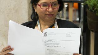 Une femme lit le projet d'accord présenté par la présidence française à l'issue de la COP21, samedi 12 décembre 2015. (MIGUEL MEDINA / AFP)
