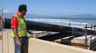 Un ingénieur de la ville du Cap supervise la construction d'une station de dessalinisation à Strandfonteinm, dans les faubourgs de la ville sud-africaine, le 19 février 2018. (KRISTIN PALITZA / DPA)
