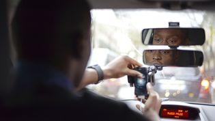 Un chauffeur UberPop dans sa voiture, à Paris, le 12 décembre 2014. (BASTIEN INZAURRALDE / SIPA)