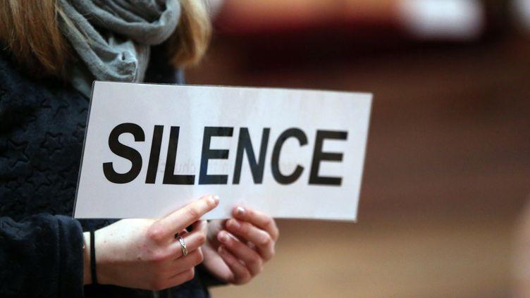 """Unpersonne tient une pancarte """"silence"""" pendant les rencontreseuropéenns de Taizé, le 3 juillet 2018, à Basel (Suisse). (GODONG / AFP)"""