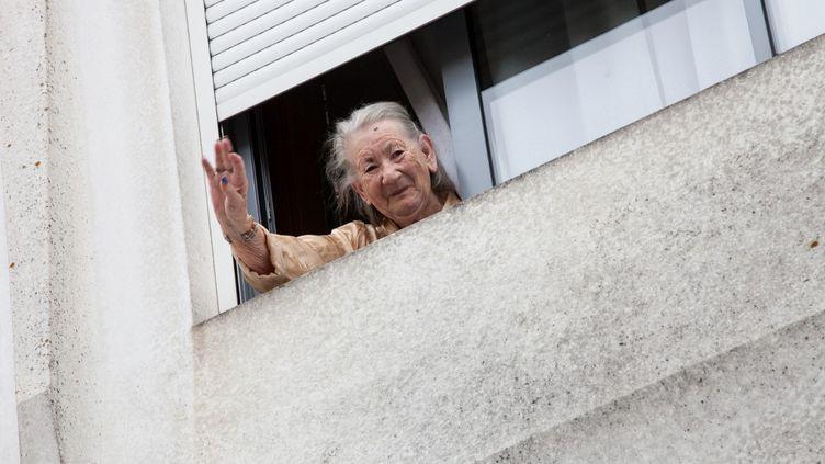 Une résidente d'un Ehpad salue un photographe de la fenêtre de sa chambre d'un Ehpad de Montauban (Tarn-et-Garonne), le 30 mars 2020. (PATRICIA HUCHOT-BOISSIER / HANS LUCAS / AFP)