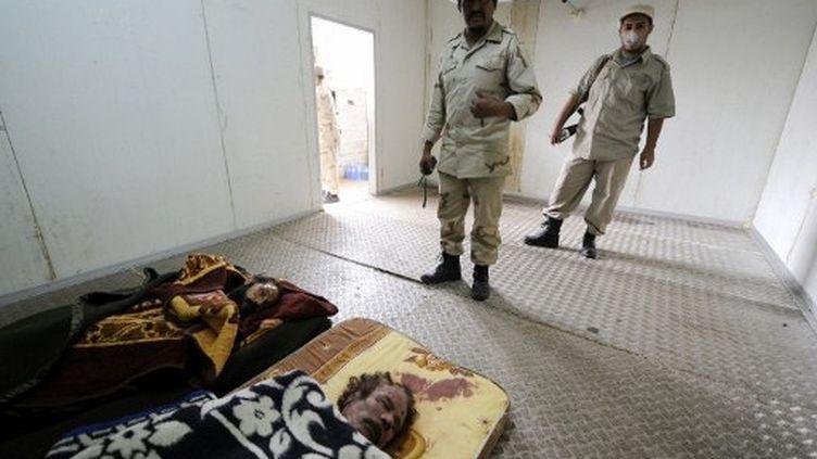 Les cadavres de Mouammar Kadhafi et de son fils Mutassem, disposés jeudi dans une chambre froide à Misrata. (PHILIPPE DESMAZES / AFP)