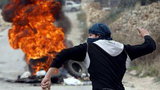 Un Palestinienjettedes pierres sur les troupes israéliennes durant des affrontements dans la ville d'Hébron, en Cisjordanie, le 6 novembre 2015. (MUSSA QAWASMA / REUTERS)