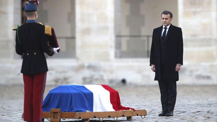 Emmanuel Macron face au cercueil de Daniel Cordier, dans la cour de l'hôtel des Invalides, jeudi 26 novembre. (MICHEL EULER / POOL / AFP)