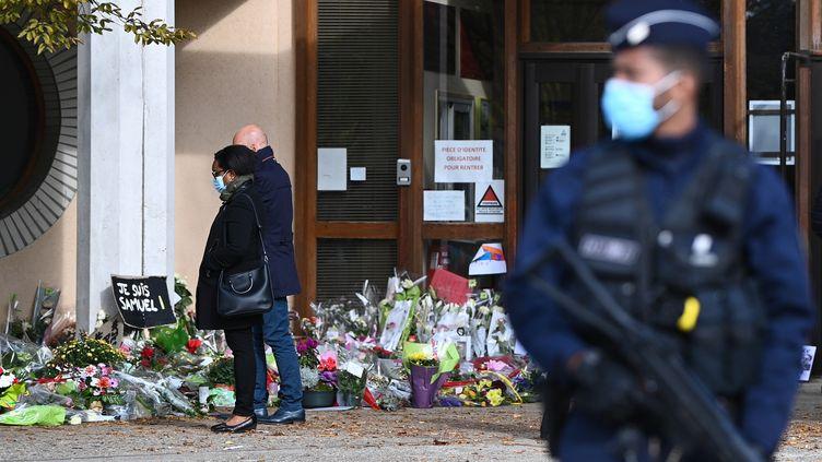 Des personnes se recueillent devant le collège du Bois d'Aulne à Conflans-Sainte-Honorine (Yvelines), le 19 octobre 2020, trois jours après l'assassinat de l'enseignant Samuel Paty. (ANNE-CHRISTINE POUJOULAT / AFP)