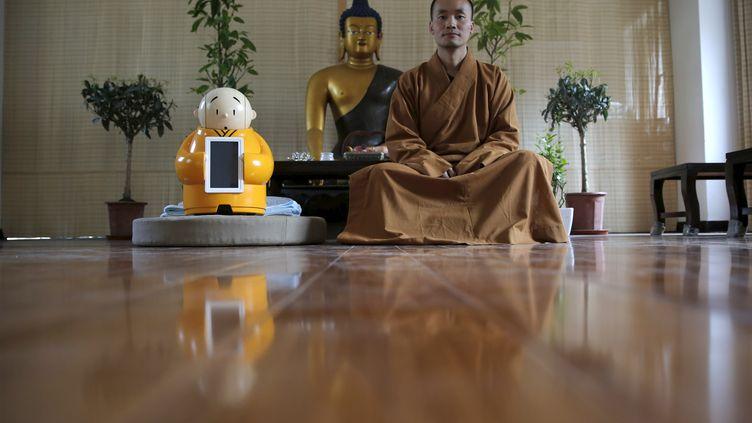 Maître Xianfan assi à côté de son robot, surnomméXian'er, dans le temple bouddhiste deLongquan, en périphérie de Pékin, le 20 avril 2016. (KIM KYUNG HOON / REUTERS)