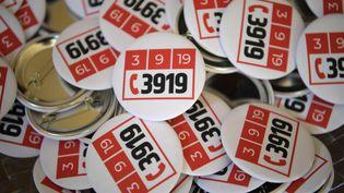 """Des badges avec le logo """"39 19"""", le numéro d'urgence dédié aux victimes de violences conjugales. (ERIC FEFERBERG / AFP)"""