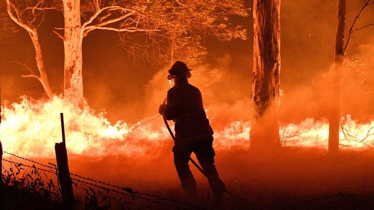 Un pompier australien combat les flammes le 31 décembre 2019 près de la ville de Nowra en Nouvelle-Galles du Sud (Australie). (SAEED KHAN / AFP)