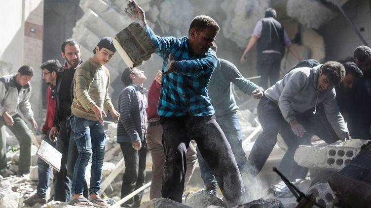 Des civils et des casques blancs suite auxattaques aériennes sur la ville rebelle de Saqba, dans l'est de Ghouta, le 4 avril.  (AMER ALMOHIBANY / AFP)