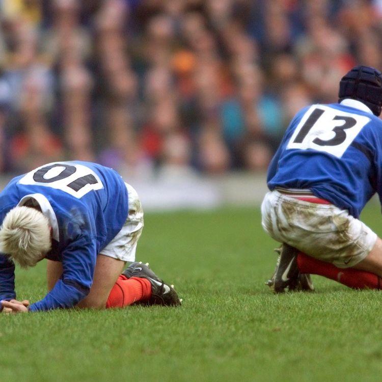 Les joueurs du XV de France, Thomas Castaignède et Pascal Giordani, récupèrent sur la pelouse de Twickenham (Londres), le 20 mars 1999. (PATRICK KOVARIK / AFP)