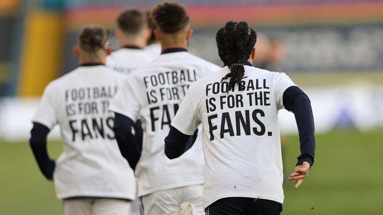"""Durant l'échauffement avant le début de la rencontre face à Liverpool le 19 avril 2021, les joueurs de Leeds ont arboré un message clair sur leur tee-shirt : """"Le football est pour les fans"""". (CLIVE BRUNSKILL / POOL)"""