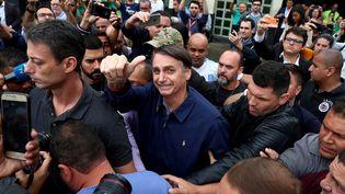 Jair Bolsonaro salue ses partisans après avoir voté au premier tour de la présidentielle, le 7 octobre 2018, à Rio de Janeiro (Brésil). (PILAR OLIVARES / REUTERS)