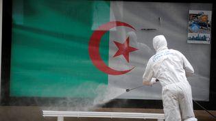 Un agent de santé désinfecte un abribus dans les rues d'Alger. L'Algérie est le pays africain qui compte à ce jour le plus grand nombre de décès liés au Covid-19. Photo prise le 20 mars 2020. (Billal Bensalem / NurPhoto / NurPhoto via AFP)