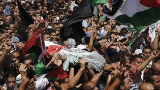 Le corps du jeune Mohamed Abou Khdeir, 16 ans, est porté par des Palestinienslors de son enterrement, le 4 juillet. Arrêté en marge du cortège, son cousin, Tarik, aurait été violemment battu par des policiers isréliens. (© FINBARR O'REILLY / REUTERS / X90055)