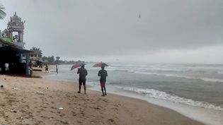Des promeneurs marchent sur la plage deTrincomalee (Sri Lanka), le 2 décembre 2020. (REUTERS)