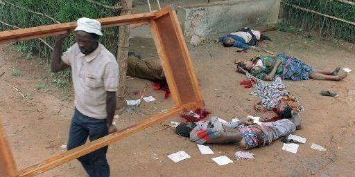 A Kigali, le 11 avril 1994. Un Rwandais récupère un cadre de lit dans une maison dont les habitants ont exécutés. (PASCAL GUYOT / AFP)
