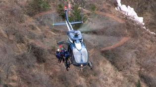 Un hélicoptère de recherche hélitreuille des gendarmes sur les lieux du crash d'un Airbus, dans les Alpes, le 24 mars 2015. (DENIS BOIS / GRIPMEDIA / AFPTV)