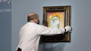 """Un employé de Sotheby's prépare le tableau """"Femme au béret rouge-orange"""" de Pablo Picasso au Bellagio, le 23 octobre 2021 à Las Vegas(Etats-Unis). (GABE GINSBERG / GETTY IMAGES NORTH AMERICA / AFP)"""