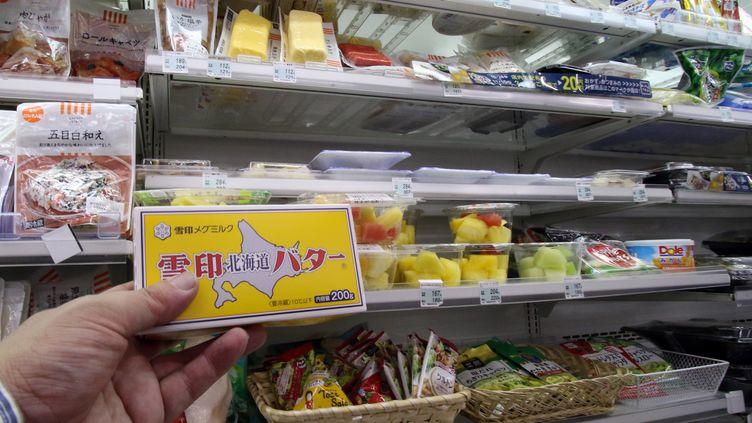 Un homme tient une plaquette de beurre dans un supermarché de Tokyo (Japon), le 10 novembre 2014. (YOSHIKAZU TSUNO / AFP)