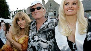 """Le fondateur de """"Playboy"""" pose entouré de son ex Barbi Benton (à gauche) et de sa compagne Holly Madison, devant son manoir à Beverly Hills en 2005. (ROBERT GALBRAITH / REUTERS)"""