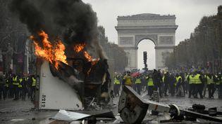 """Un véhicule de chantier est incendié sur les Champs-Elysées, le 24 novembre 2018, à Paris, lors d'une manifestation des """"gilets jaunes"""". (BERTRAND GUAY / AFP)"""